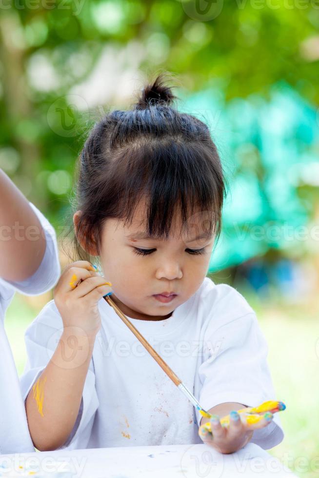 bambino dipinto, ragazza carina sta dipingendo sulla sua mano foto