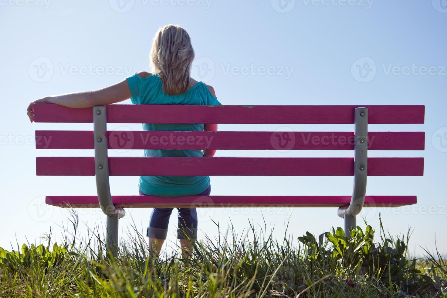 donna in blu, seduta su una panchina rosa in zona rurale foto