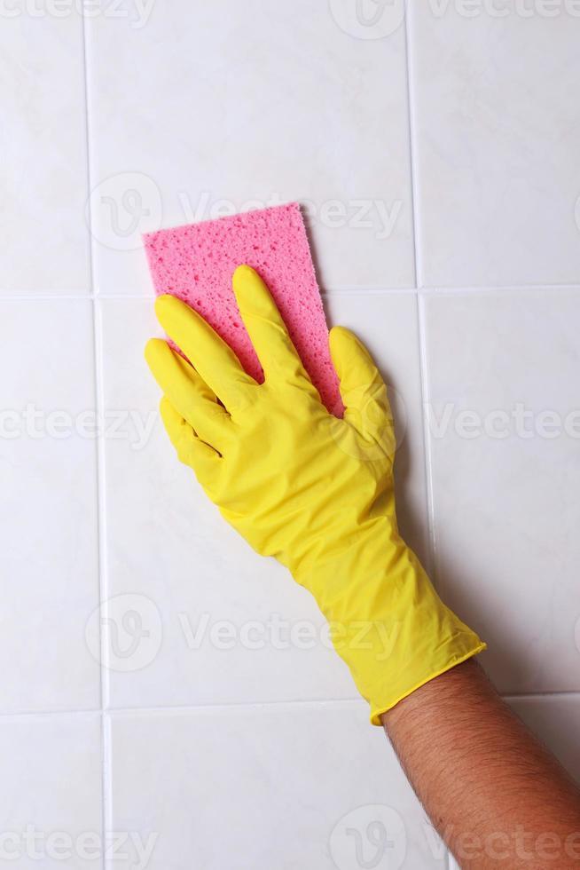 pulizia piastrelle della cucina con spugna foto