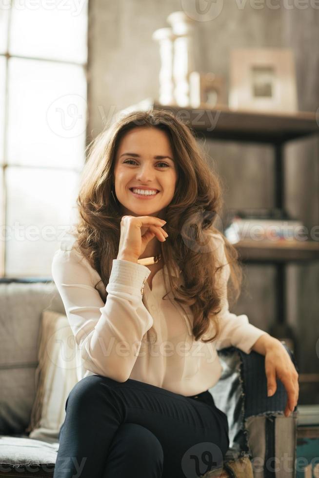 giovane donna sorridente che si siede sul divano in appartamento loft foto