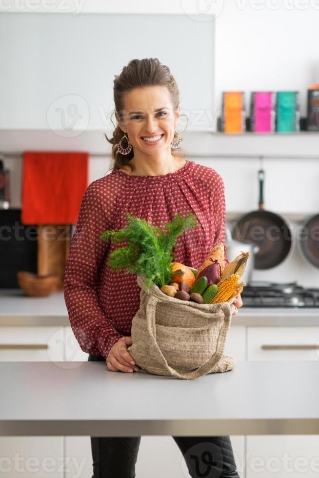felice casalinga giovane con acquisti sul mercato locale in cucina foto