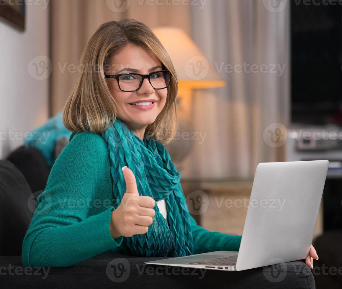 giovane donna felice che per mezzo del computer portatile a casa foto