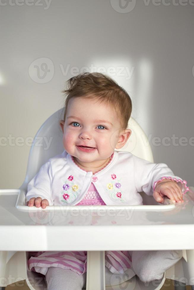 bambino allegro nel seggiolone foto