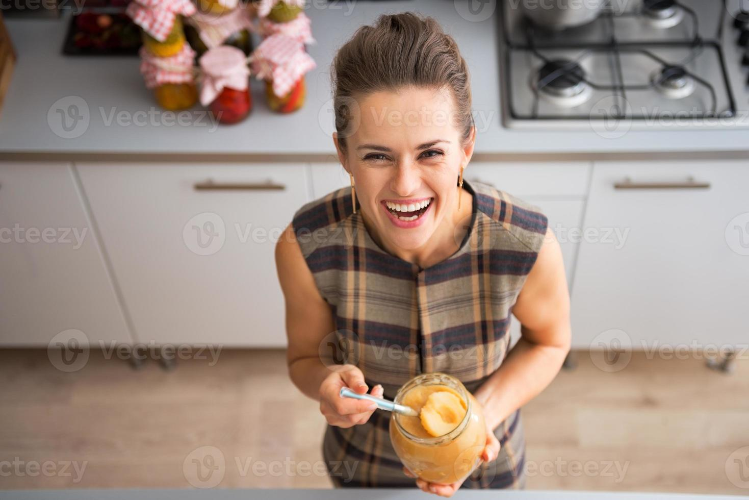Ritratto di giovane casalinga felice tenendo il barattolo con marmellata di mele foto