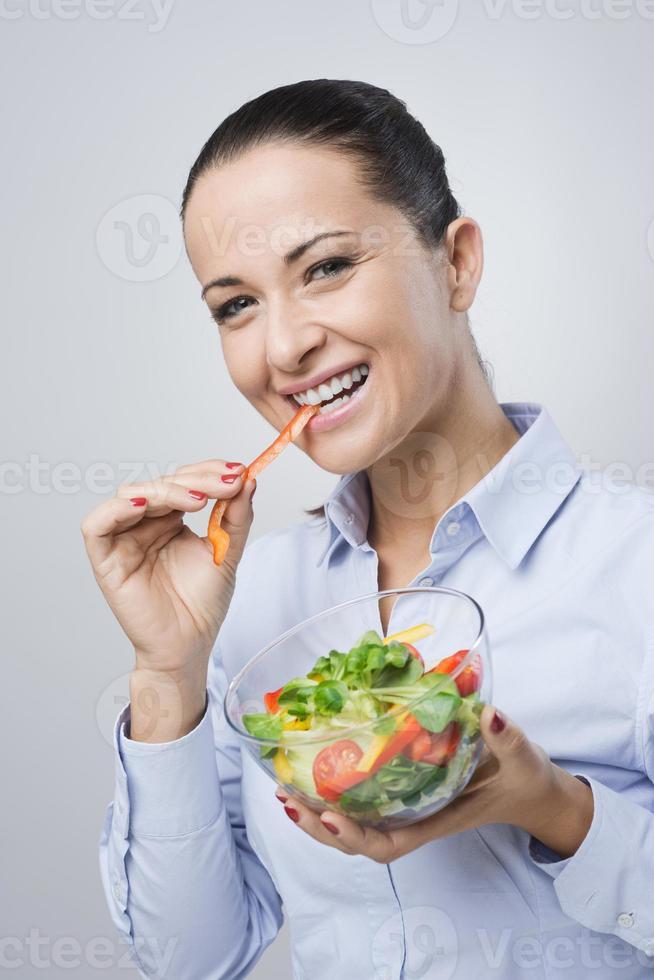 donna allegra che mangia insalata foto