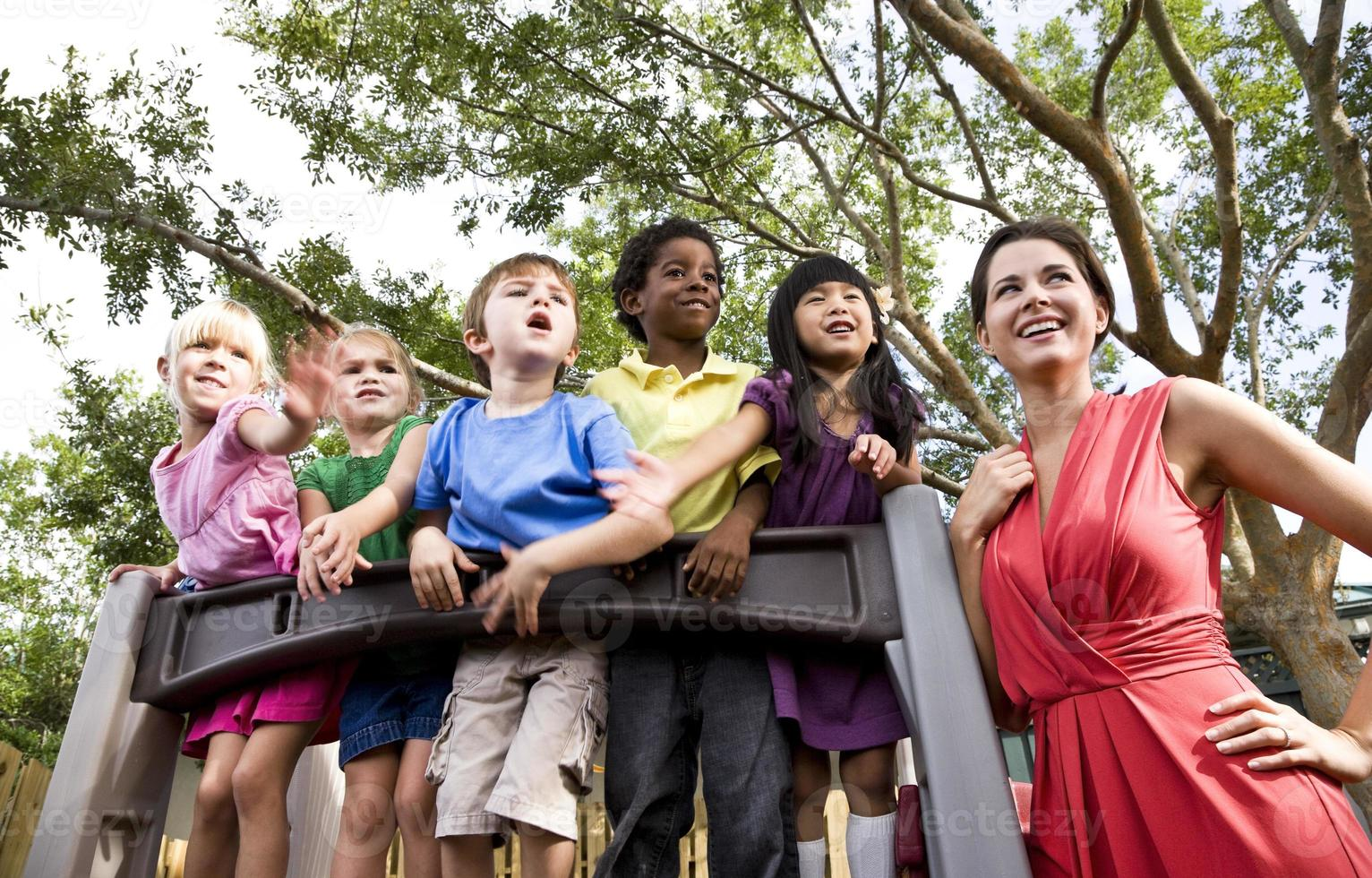 insegnante di scuola materna con gli studenti sul parco giochi guardando fuori foto