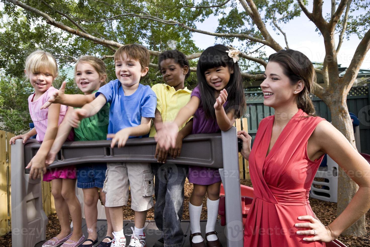 bambini in età prescolare che giocano nel parco giochi con l'insegnante foto