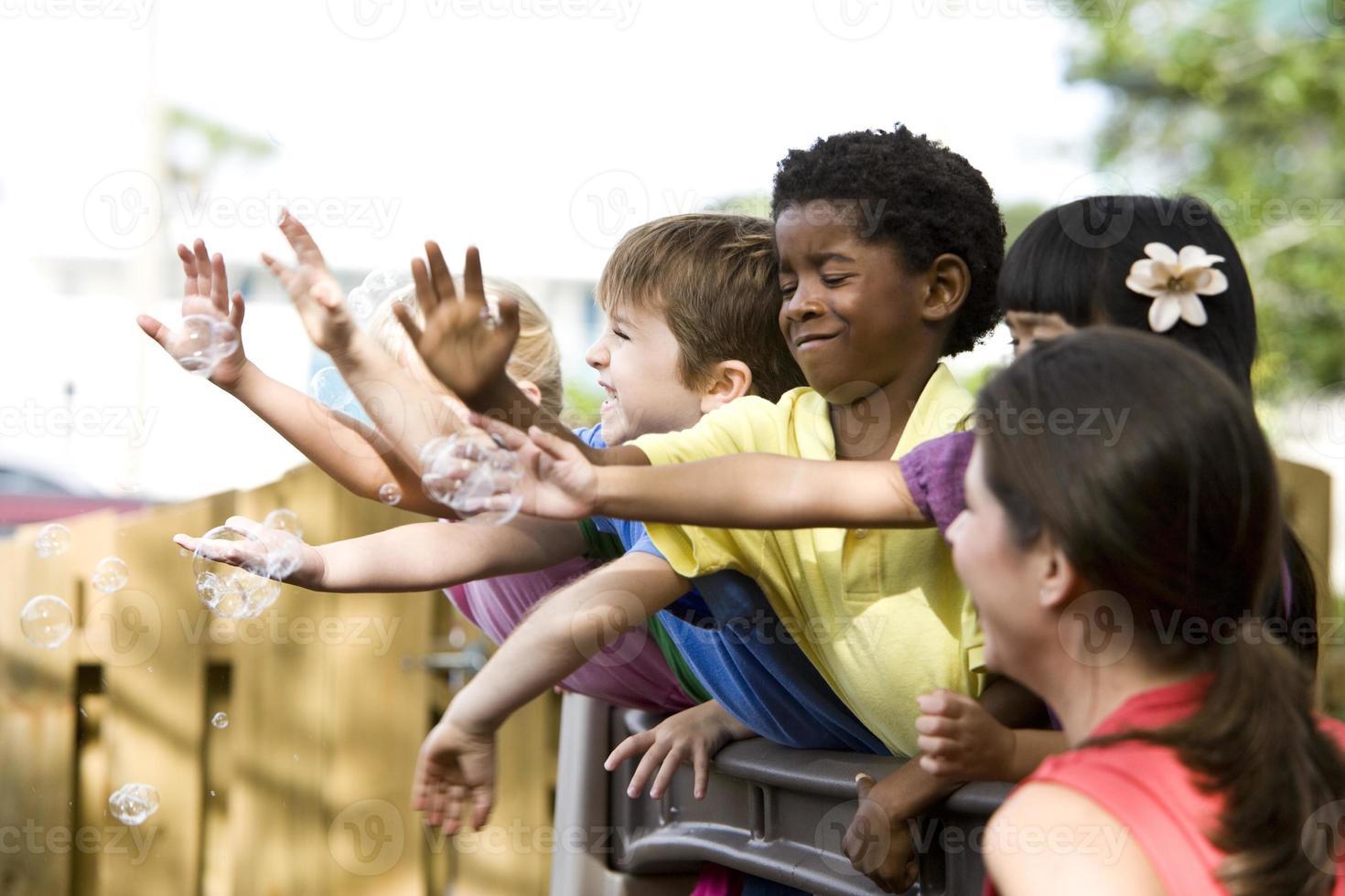 gruppo eterogeneo di bambini in età prescolare che giocano all'asilo con l'insegnante foto