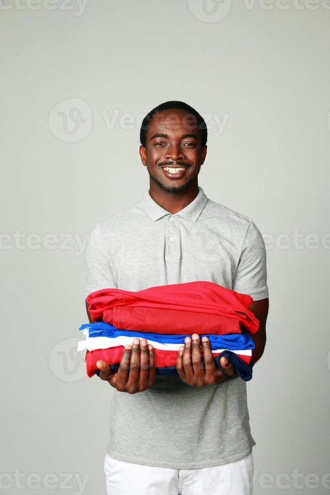 uomo africano allegro che tiene i suoi vestiti foto