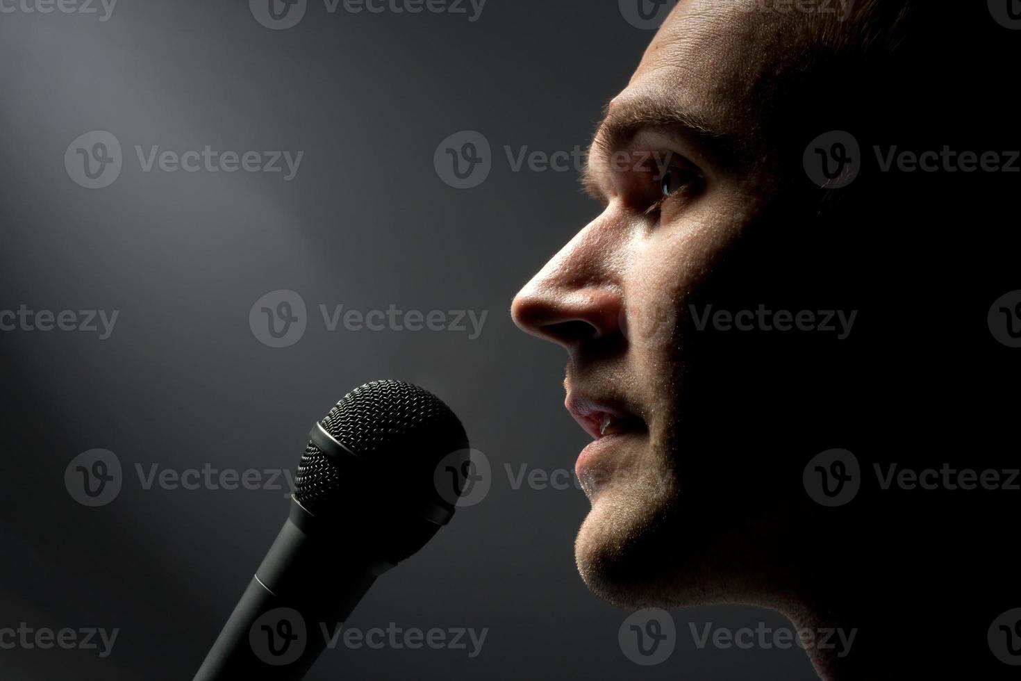 uomo che canta al microfono foto