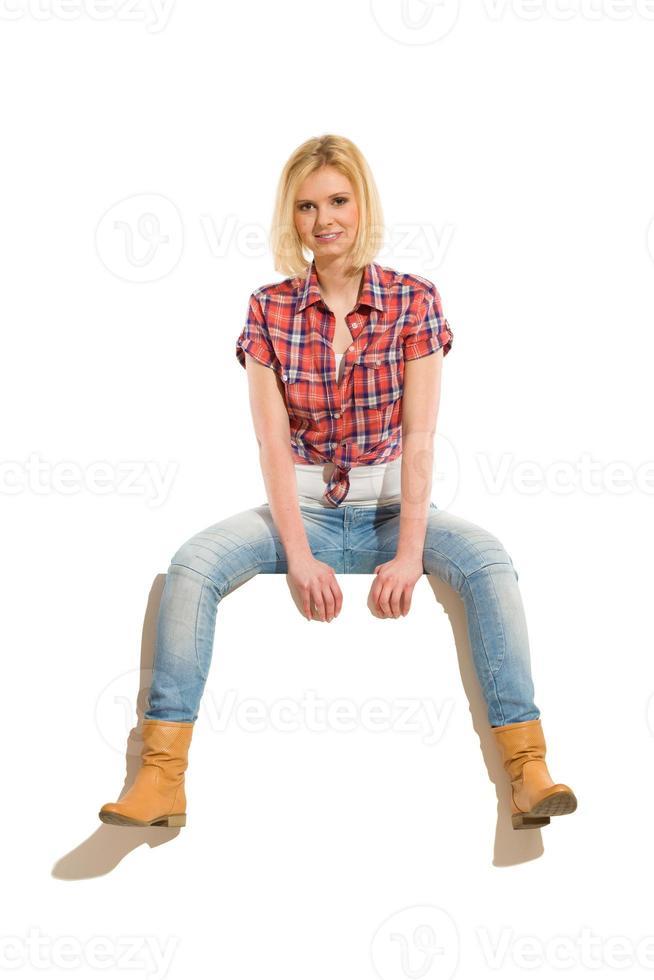 giovane donna allegra che si siede su un'insegna foto