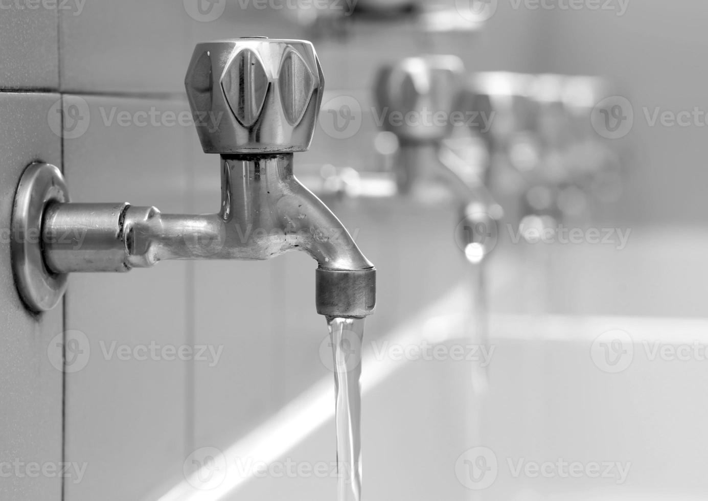 rubinetti aperti con acqua che scorre negli spogliatoi del bagno foto