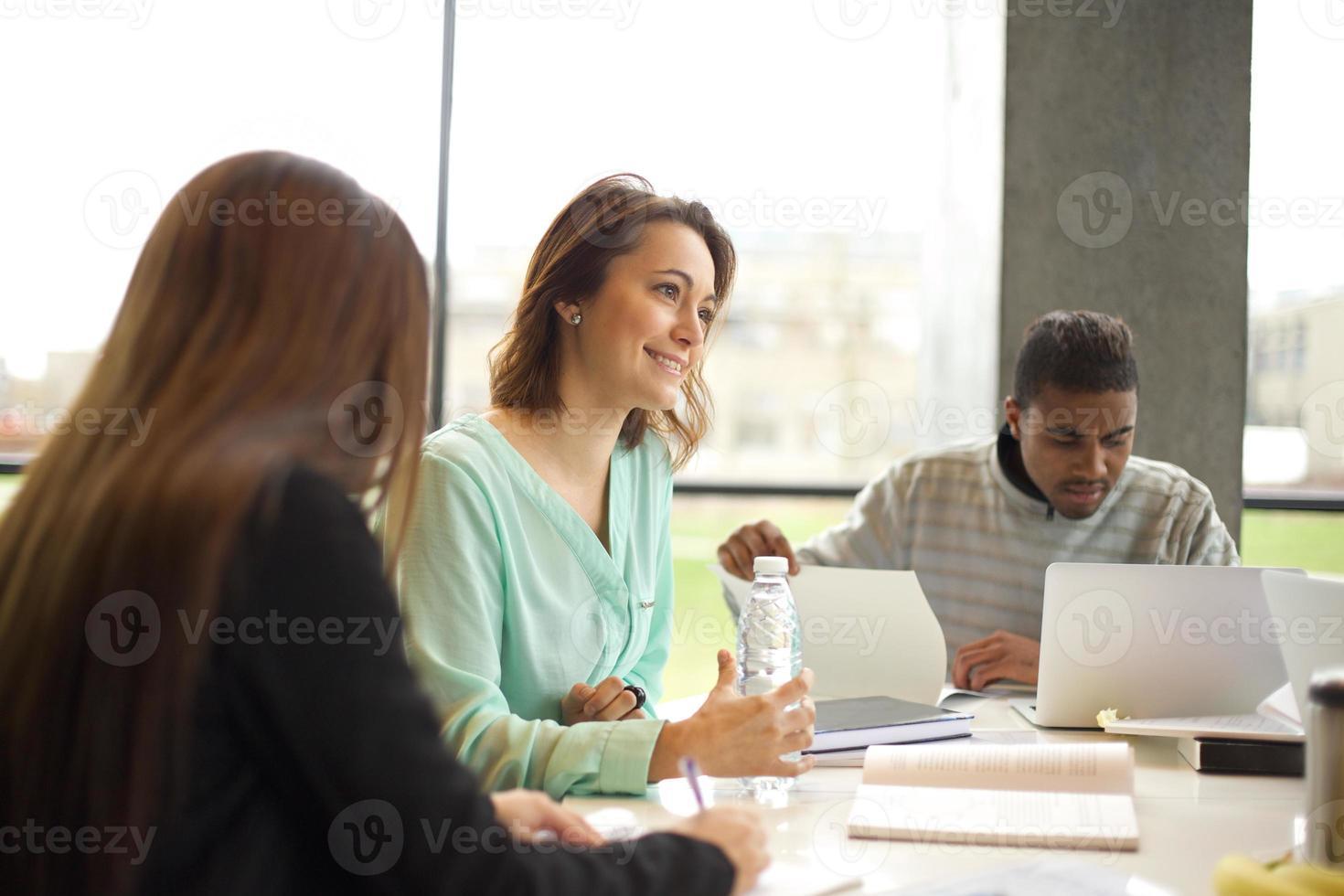 giovane donna che studia in biblioteca con altri studenti foto