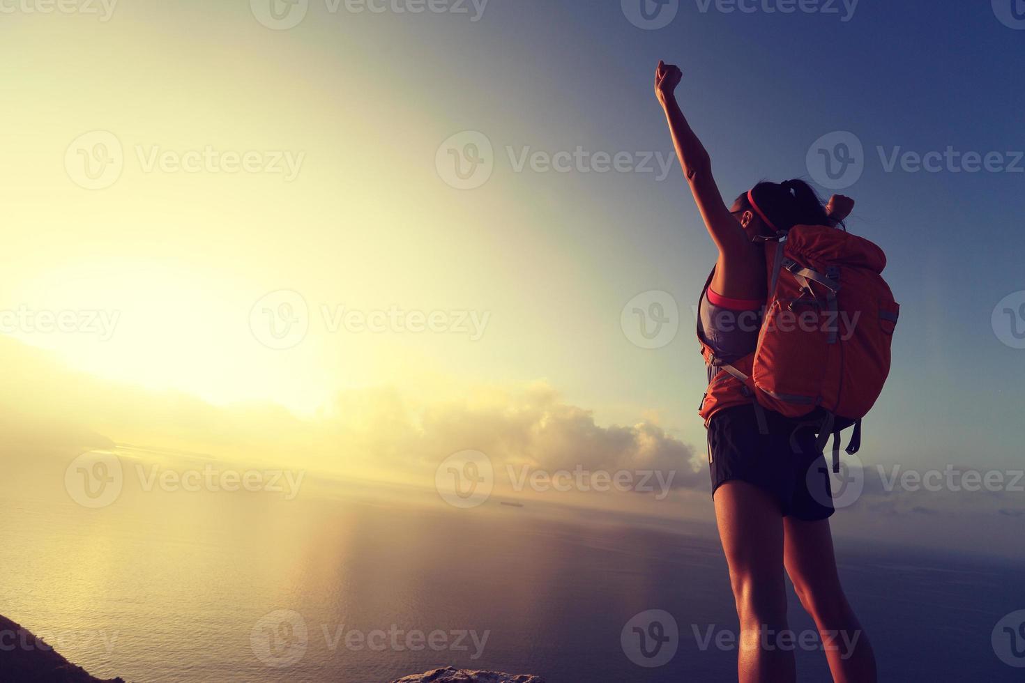 Viaggiatore con zaino e sacco a pelo incoraggiante della giovane donna al picco di montagna del mare di alba foto