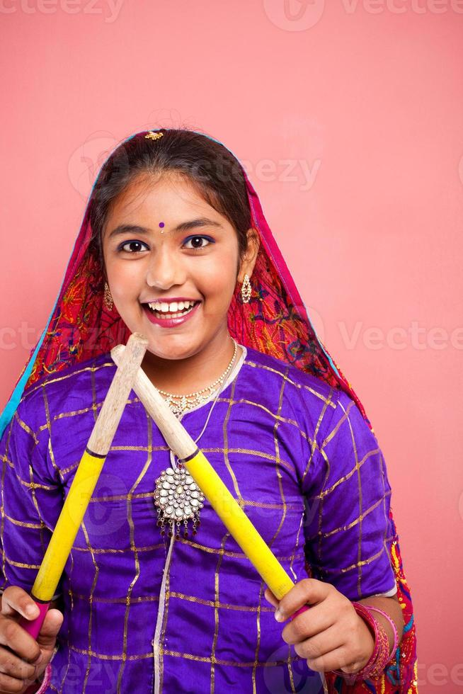 bella ragazza adolescente indiana attraente allegra che tiene bastoni dandiya foto
