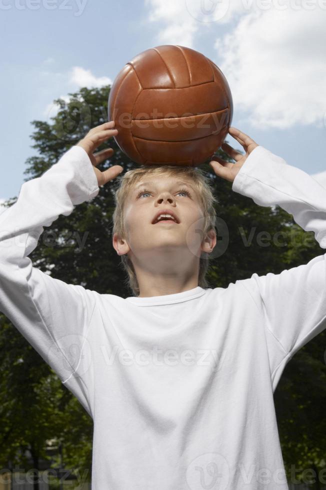 ragazzo in piedi con un pallone da basket in testa. foto