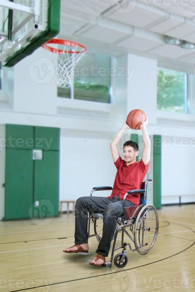 giocatore che lancia la palla al canestro foto