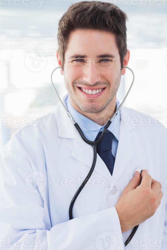 medico allegro con il suo sguardo dello stetoscopio foto