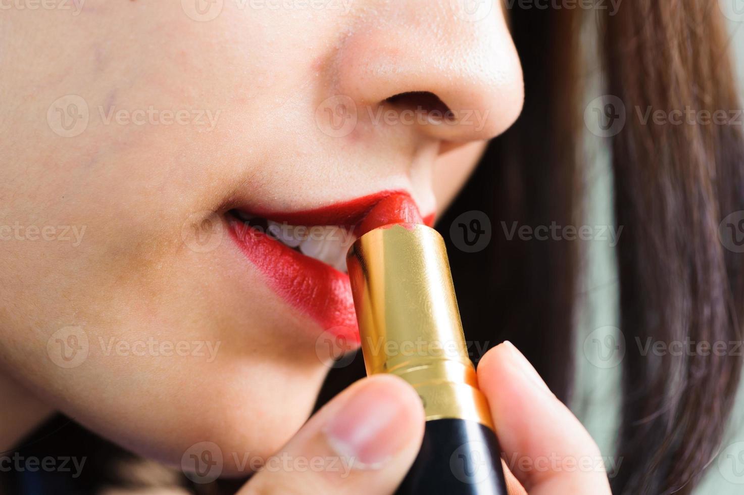 la giovane donna applica il rossetto rosso foto