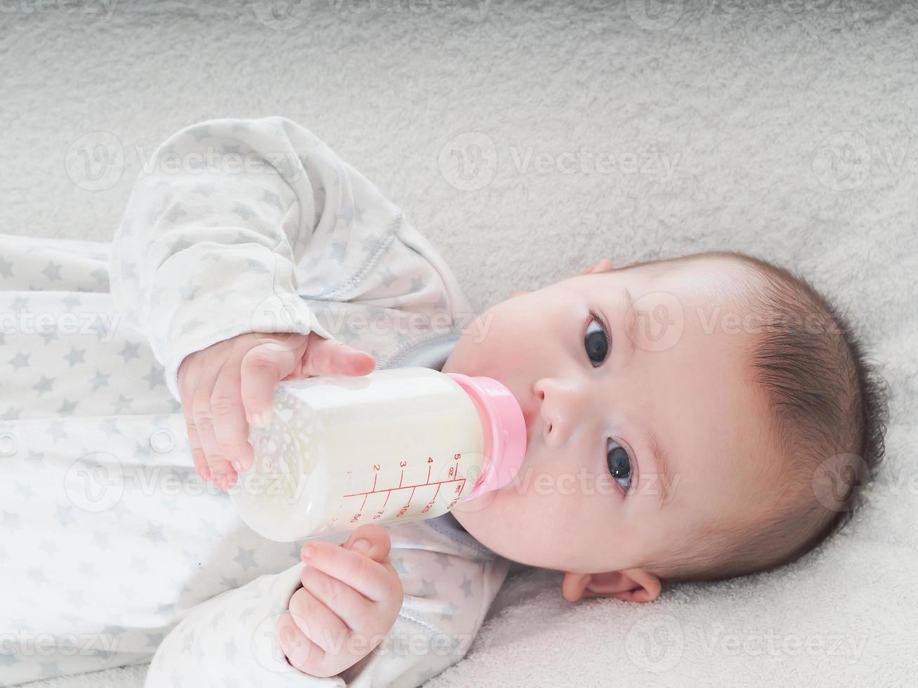bambino che beve latte dalla bottiglia a casa foto