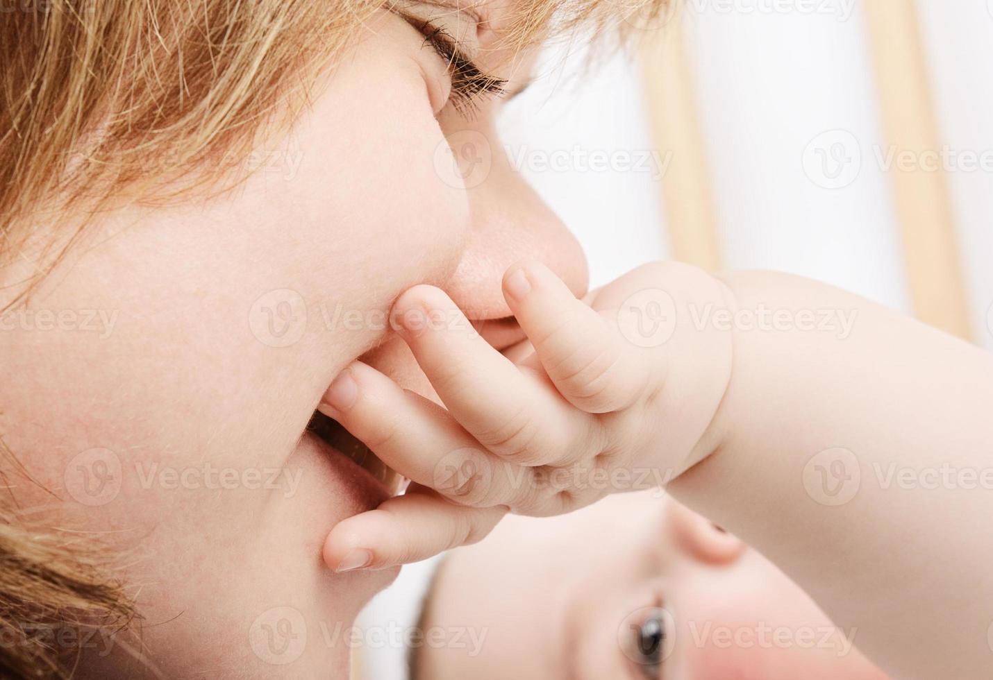 mamma che bacia la piccola mano del bambino foto