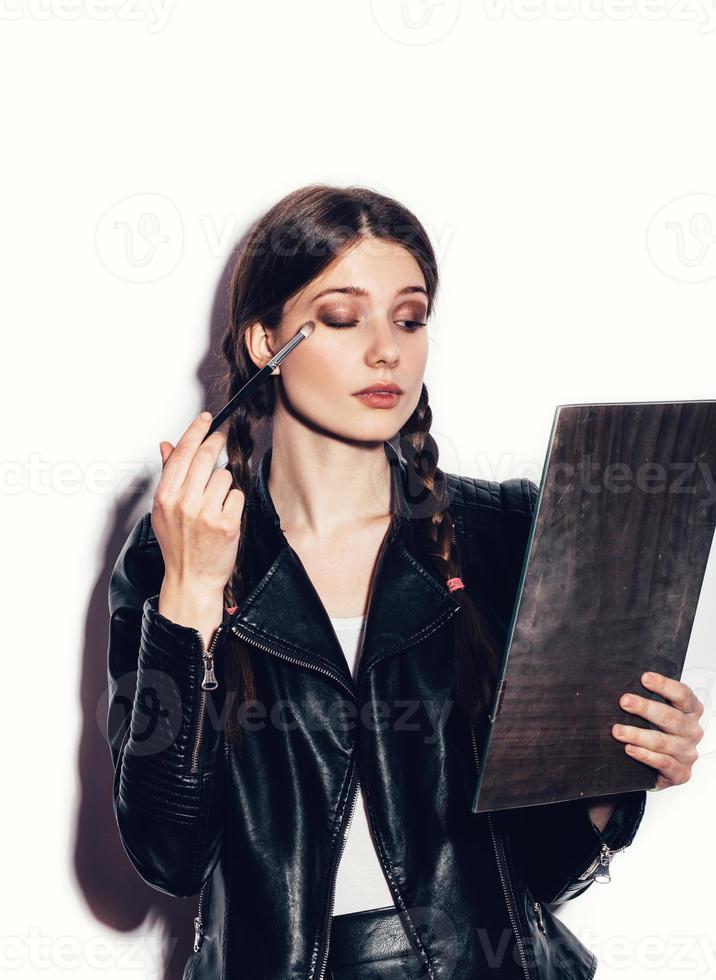 donna guardarsi allo specchio e applicare cosmetici foto