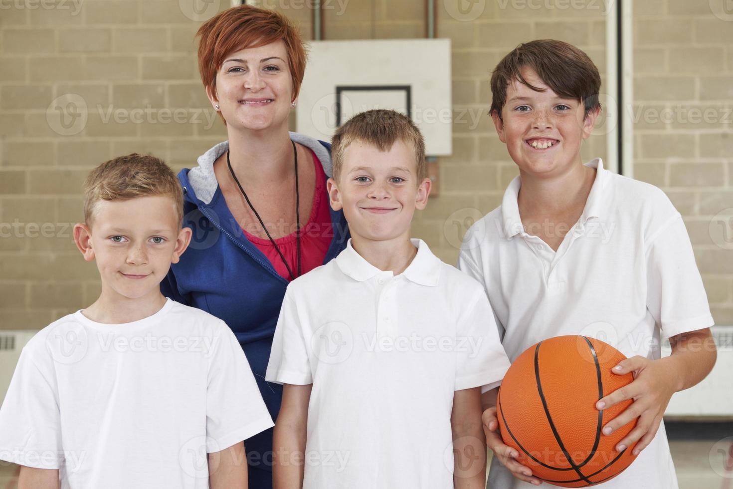 insegnante con la squadra di pallacanestro della scuola dei ragazzi foto