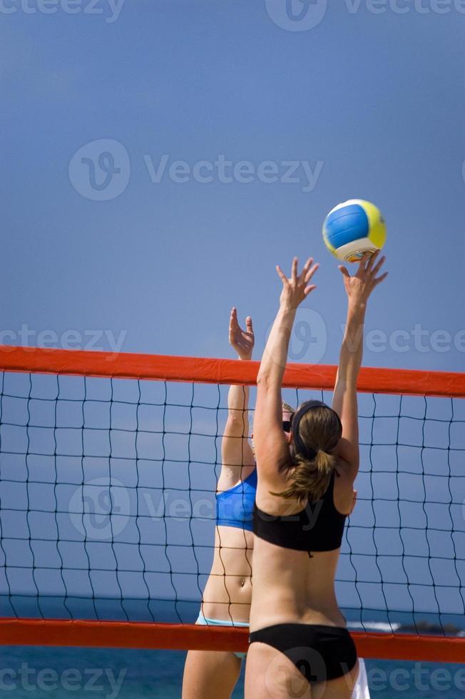 due donne che giocano a beach volley foto