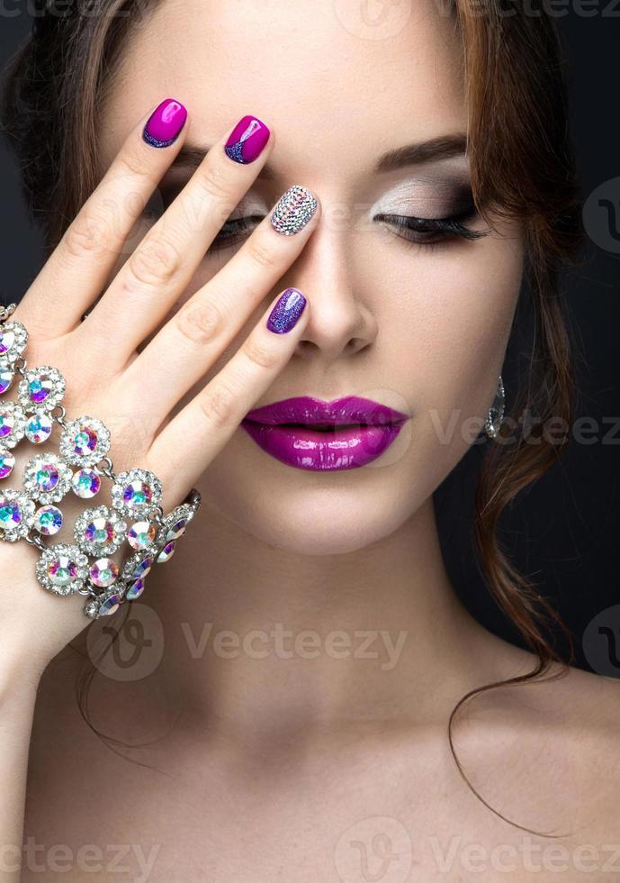ragazza con trucco luminoso e manicure viola con strass foto