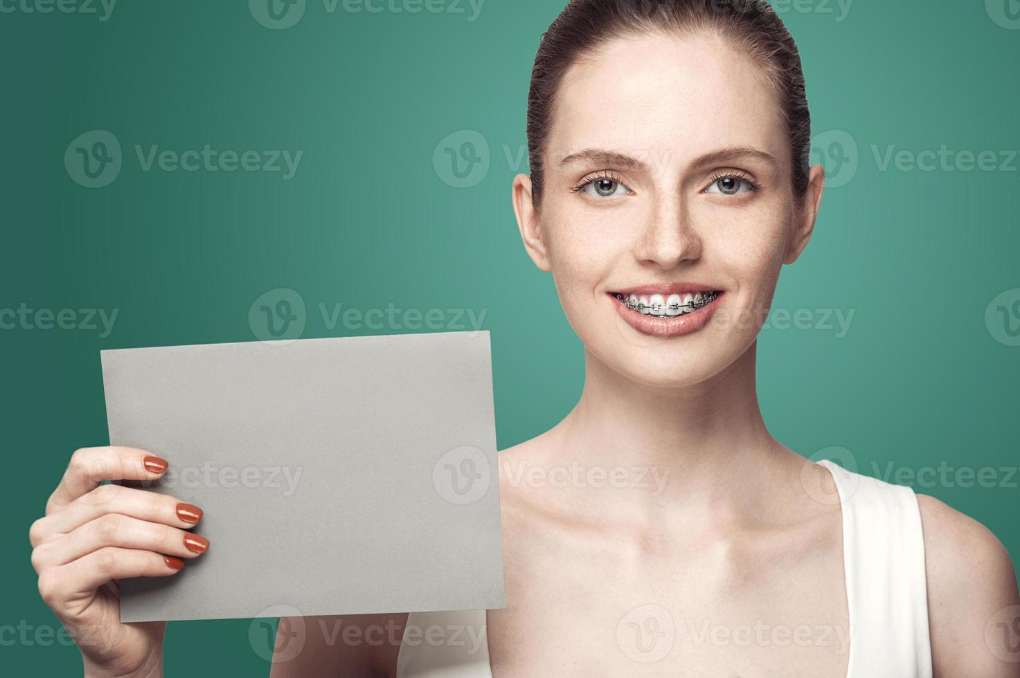 bella ragazza con bretelle e carta grigia nelle mani foto