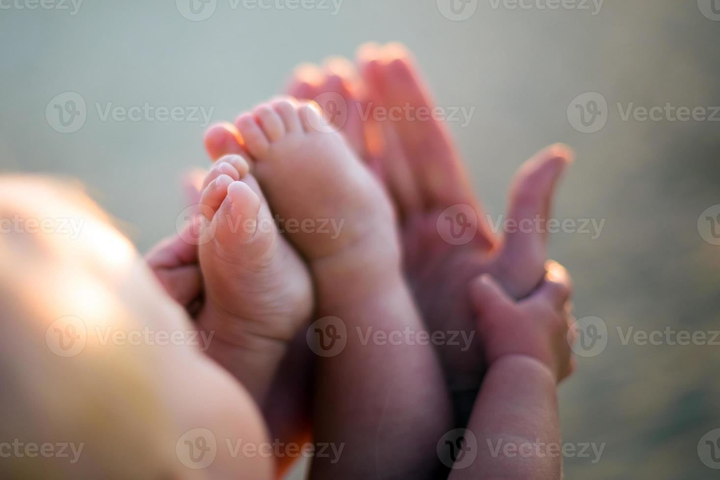 piccoli piedi del bambino sulle mani delle madri all'aperto a backligh foto