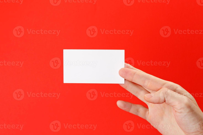 la mano dell'uomo d'affari che tiene il biglietto da visita in bianco del Libro Bianco foto