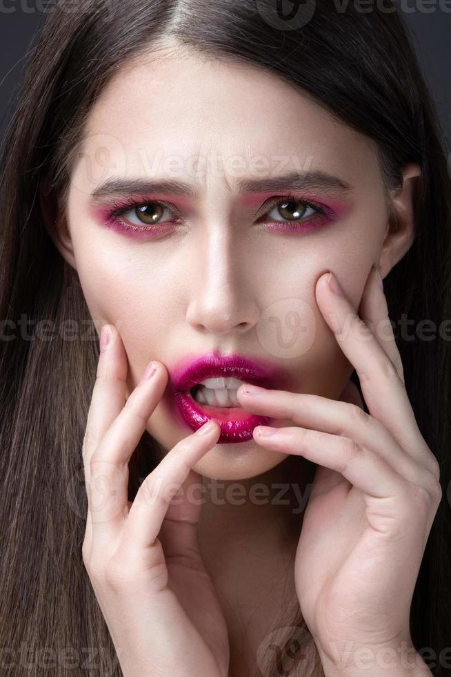 ragazza con rossetto rosa spalmato sul viso. foto