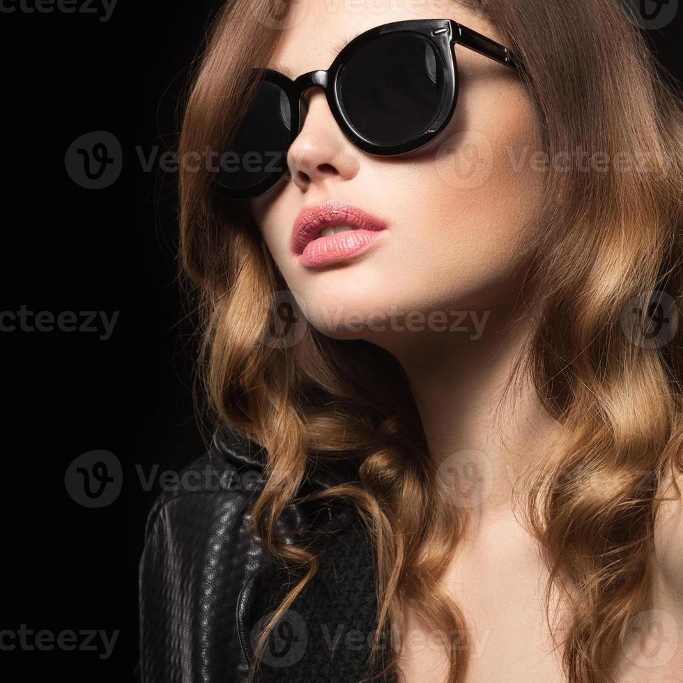 ragazza in occhiali da sole scuri, con riccioli e trucco da sera. foto