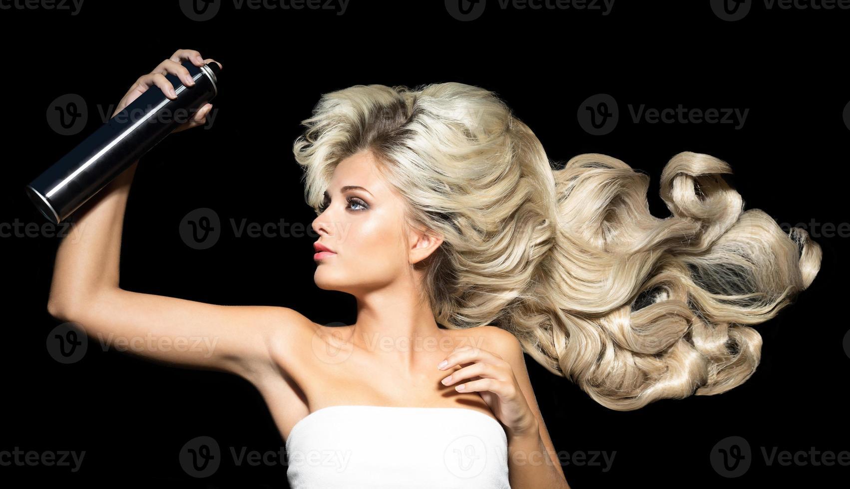 donna bionda con una lacca per capelli foto