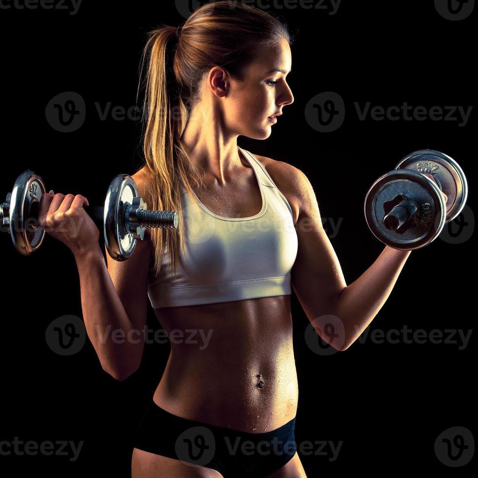 ragazza fitness - attraente giovane donna che lavora con manubri foto