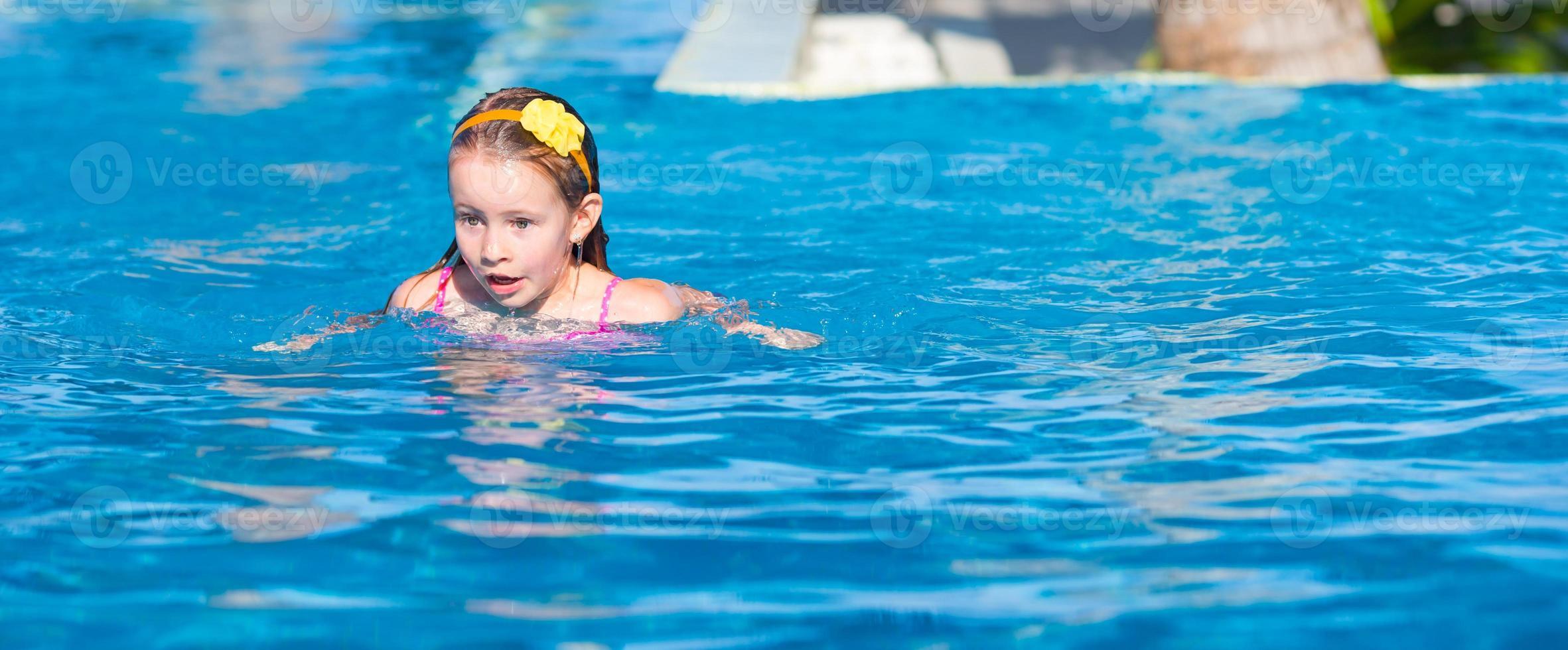 adorabile bambina nella piscina all'aperto foto