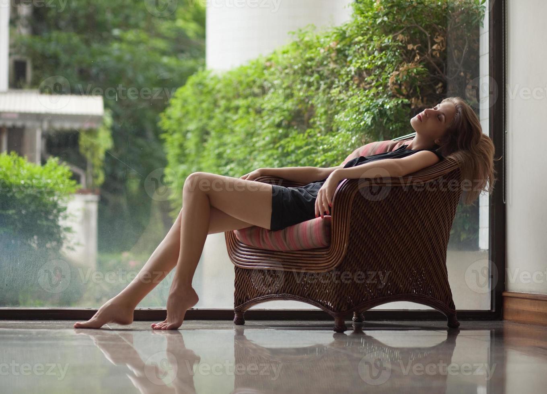 donna che si distende su una sedia foto