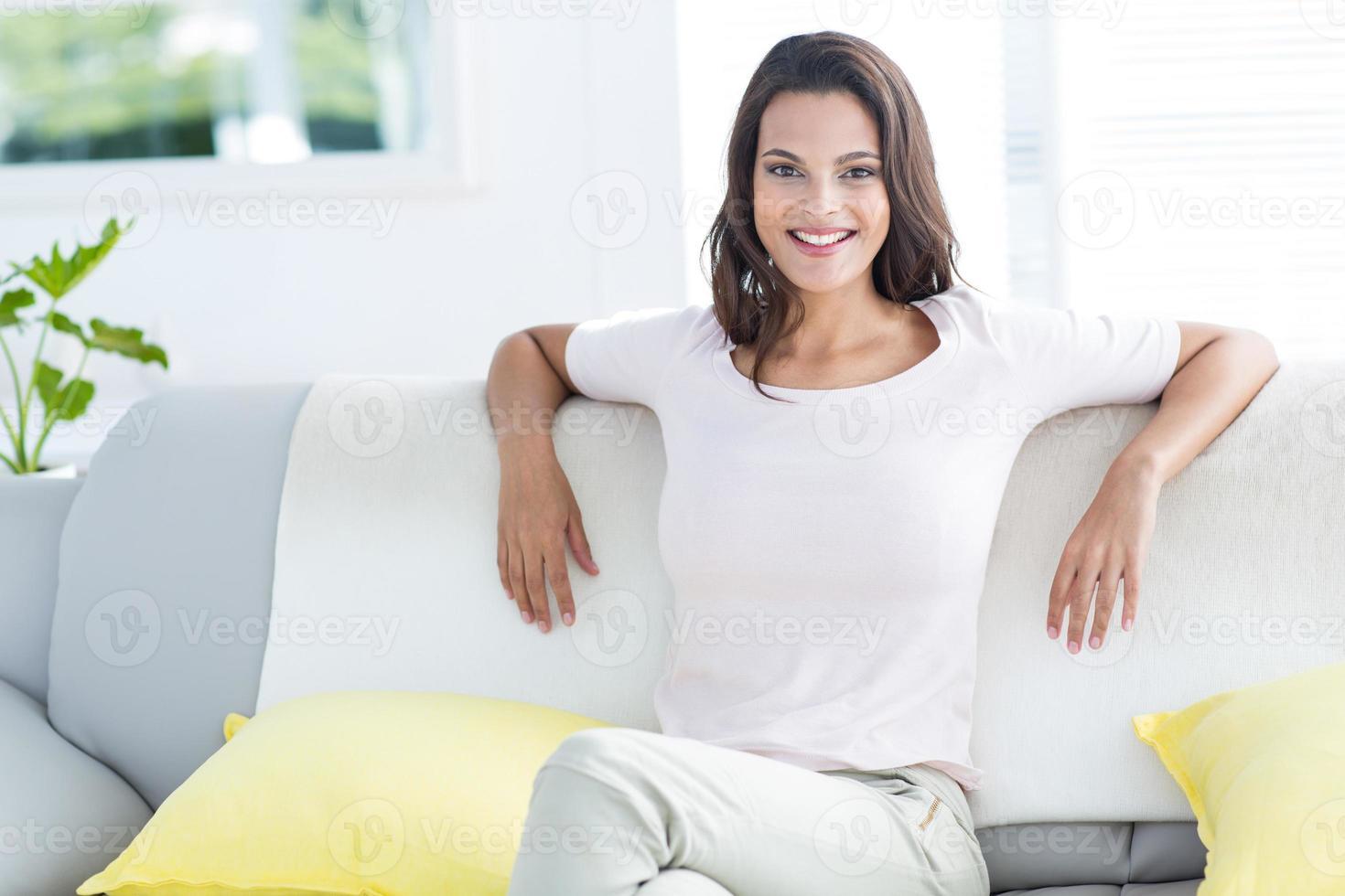 sorridente bella bruna rilassante sul divano foto