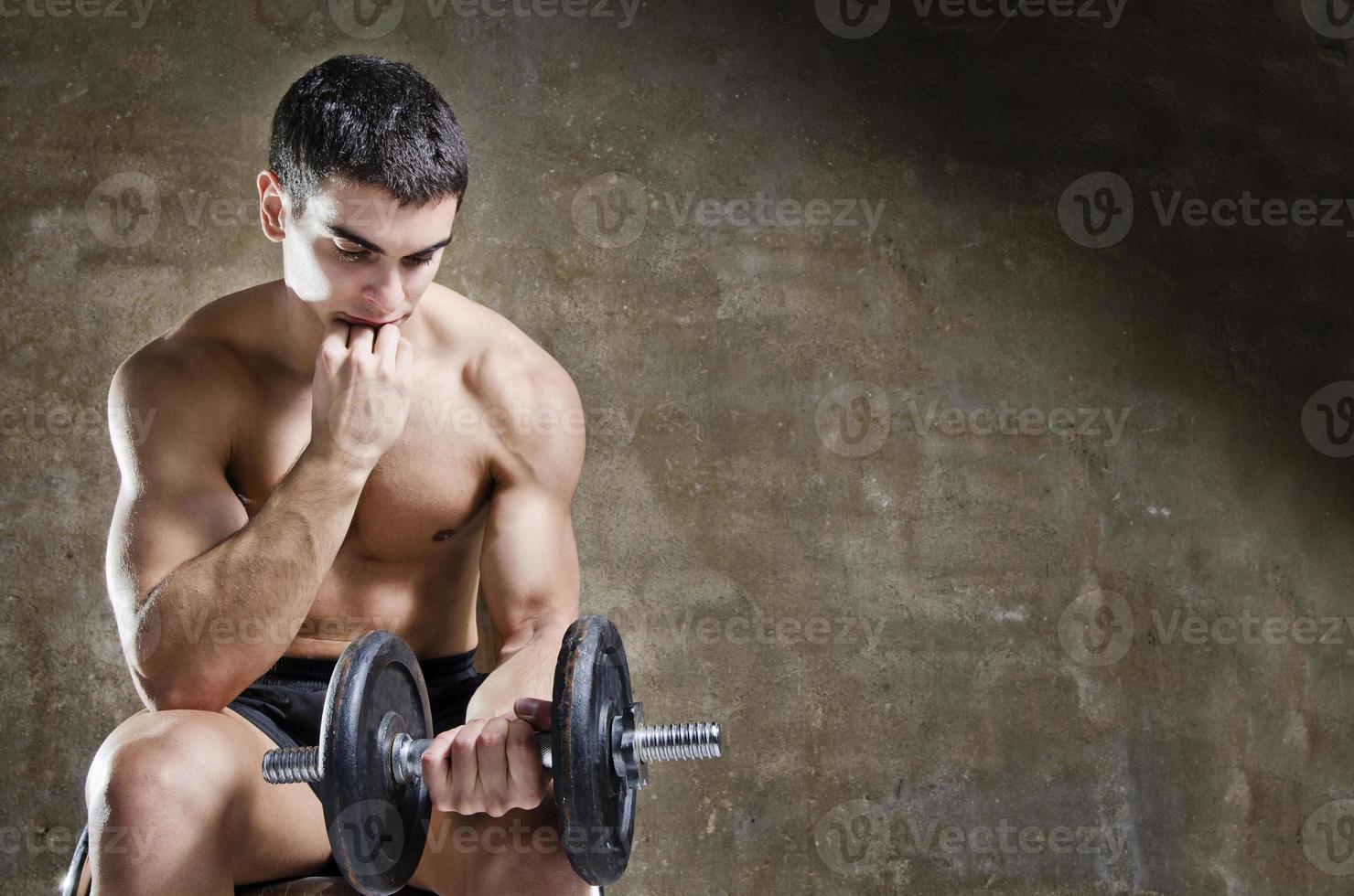 uomo riflessivo e rilassato allenamento con manubri foto
