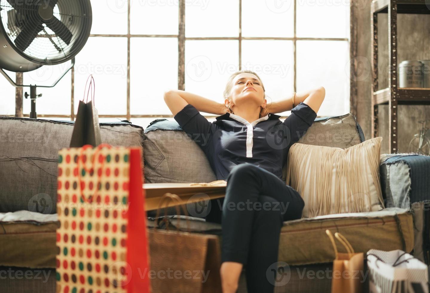 giovane donna rilassata con i sacchetti della spesa che si siedono in appartamento del sottotetto foto