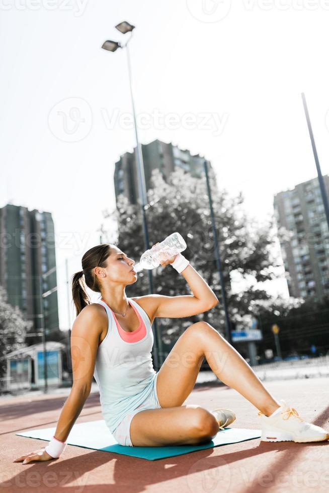 acqua potabile della giovane bella donna dopo l'esercizio in una città foto