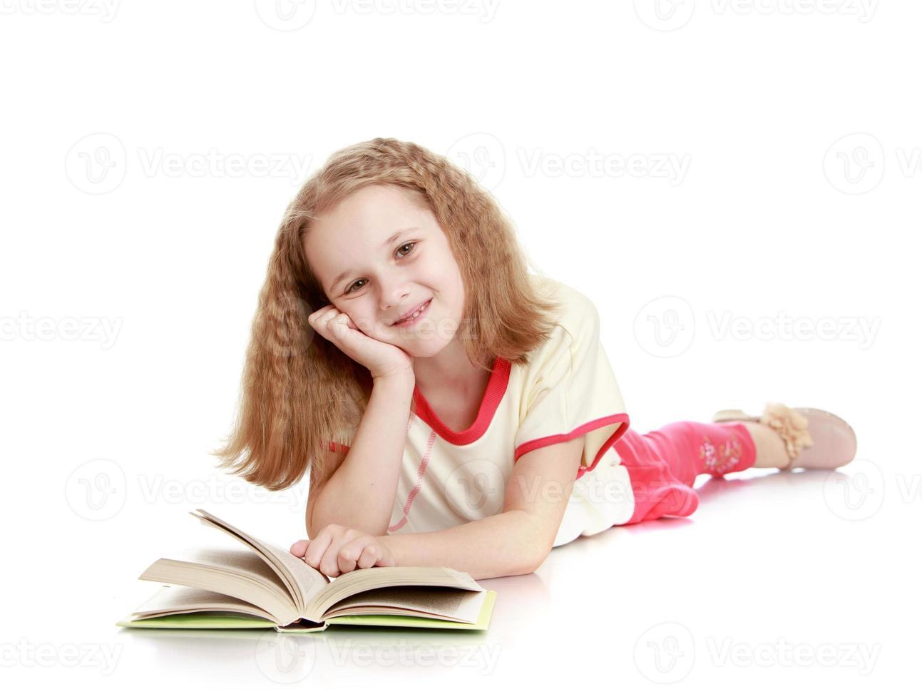 la ragazza giace sul pavimento e legge un libro foto