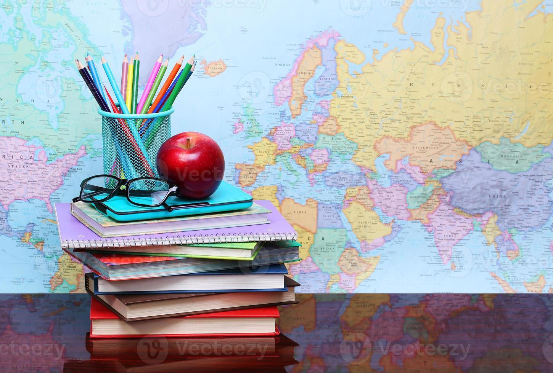 di nuovo a scuola. una mela, matite colorate, bicchieri e libri foto