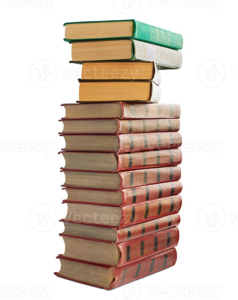 pila di vecchi libri con timbratura d'oro su sfondo bianco foto