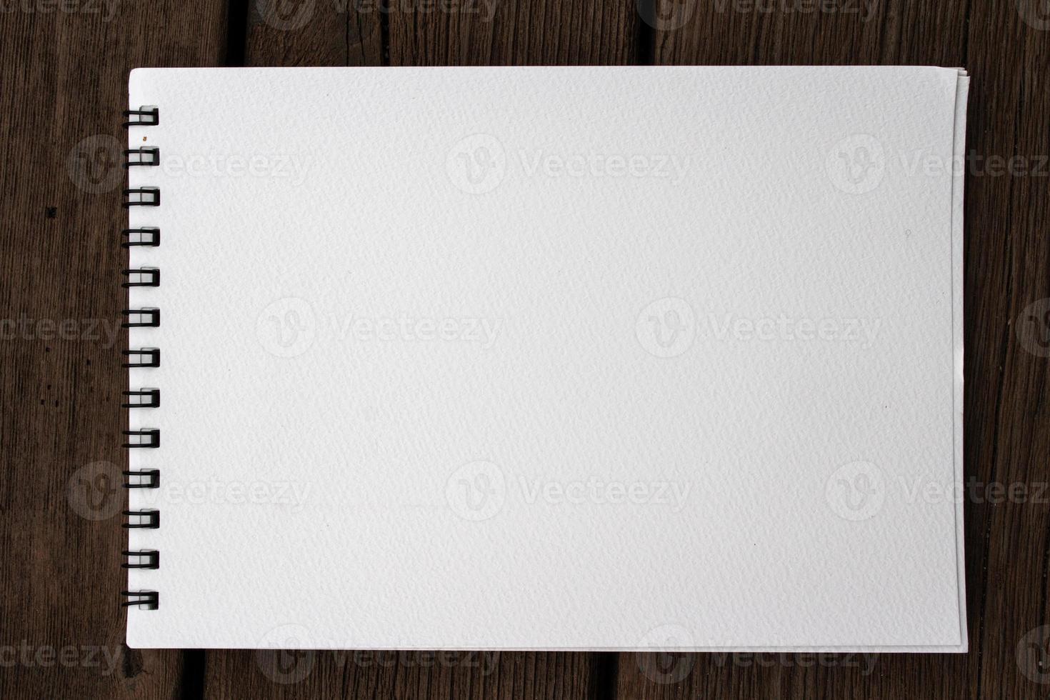 taccuino realistico del blocco note a spirale di carta in bianco dello stagno sul banco di legno foto
