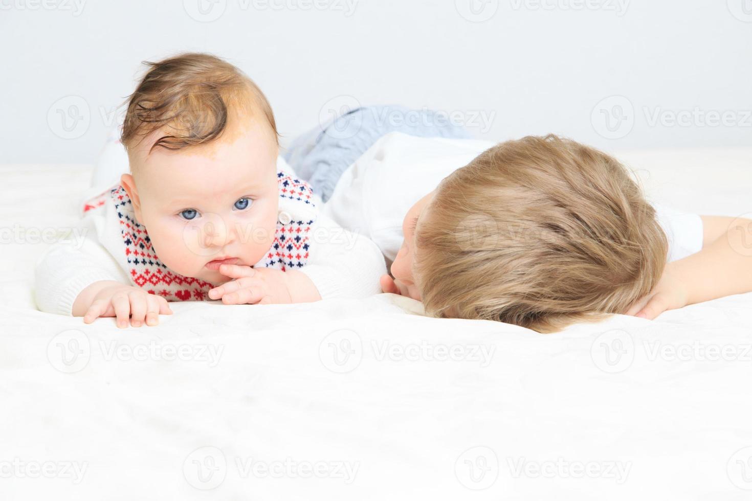 ragazzino che tiene a mano sorella neonata foto