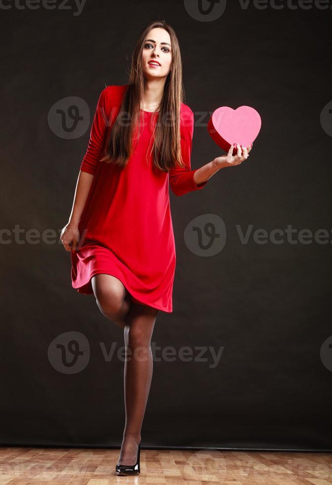 donna che tiene il cuore in abito rosso. foto