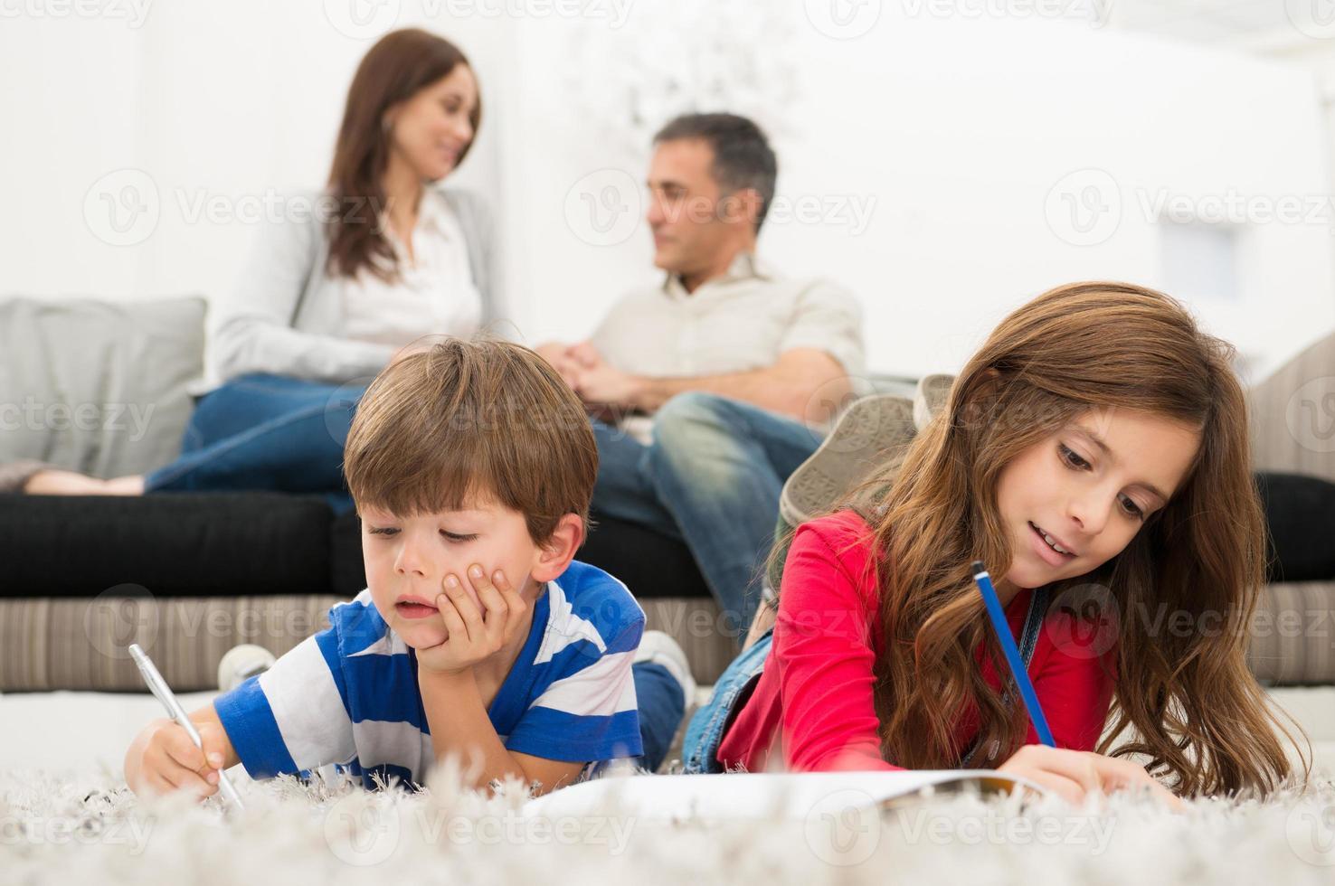 bambini che studiano sdraiati sul pavimento foto