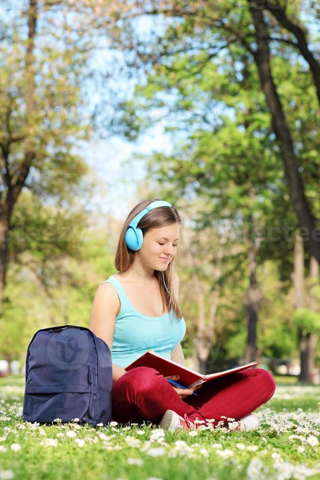 giovane donna che studia nel parco foto